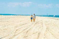 Jeune marche américaine de couples, détendant sur la plage dans nouveau Jers Image libre de droits