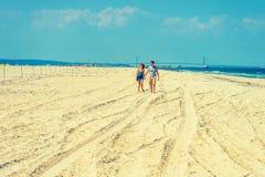 Jeune marche de couples, détendant sur la plage dans le New Jersey, les Etats-Unis Image libre de droits