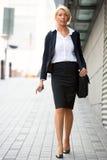 Jeune marche de femme d'affaires photos stock