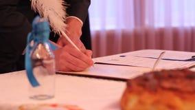 Jeune marié signant d'une manière ordonnée le certificat de mariage, couple dans l'amour créant la famille banque de vidéos