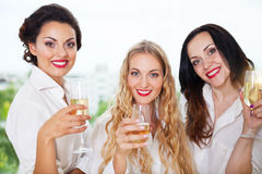 Jeune mariée à être et bridemaids jugeant en verre avec le champagne Photographie stock
