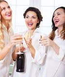 Jeune mariée à être et bridemaids jugeant en verre avec le champagne Photo stock