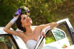 Jeune mariée à côté d'une voiture Photo libre de droits