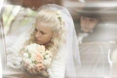 Jeune mariée à la fenêtre au mariage photographie stock