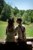 Jeune mariée élégante de couples de mariage dans la robe blanche et le marié élégant s'asseyant sur un banc en parc images libres de droits