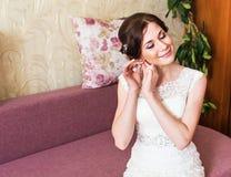 Jeune mariée élégante mettant sur le plan rapproché de boucles d'oreille, se préparant à épouser Photo libre de droits