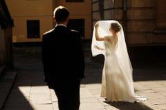 Jeune mariée élégante tenant le voile et posant avec l'und de marié au soleil Image libre de droits