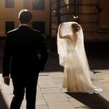 Jeune mariée élégante tenant le voile et posant avec l'und de marié au soleil Photo libre de droits
