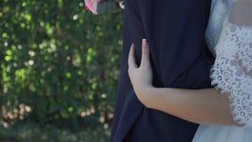 Jeune mariée étreignant le marié à la taille avec un bouquet dans des mains banque de vidéos