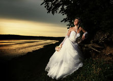 Jeune mariée admirant le coucher du soleil Photo stock