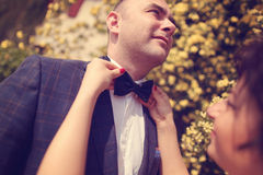 Jeune mariée aidant le marié avec le bowtie Photos stock