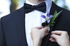 Jeune mariée ajustant le boutonniere sur la veste de mariés photo libre de droits