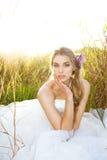 Jeune mariée attirante s'asseyant dans l'herbe image stock