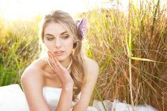 Jeune mariée attirante s'asseyant dans l'herbe photos libres de droits