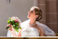 Jeune mariée au mariage dans l'église avec le bouquet de fleur Image libre de droits