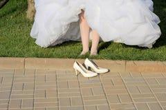 Jeune mariée aux pieds nus et ses chaussures Image libre de droits