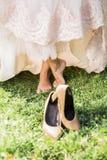 Jeune mariée aux pieds nus sur l'herbe avec des chaussures Photos libres de droits