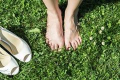Jeune mariée aux pieds nus sur l'herbe dans l'heure d'été Photo stock