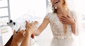 Jeune mariée avec des amis buvant du champagne dans la boutique nuptiale Photographie stock