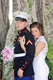 Jeune mariée avec des bras autour de marié de militaires Image libre de droits
