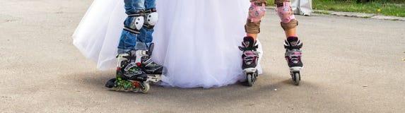 Jeune mariée avec des enfants sur des patins de rouleau Photo stock