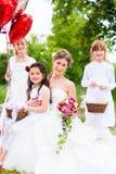 Jeune mariée avec des filles comme demoiselles d'honneur, fleurs et ballons Photographie stock libre de droits
