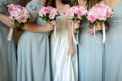 Jeune mariée avec des fleurs et des domestiques Image libre de droits