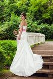 Jeune mariée avec du charme dans une robe de mariage blanche restant sur le pont Photo stock
