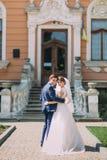 Jeune mariée avec du charme nouvellement romantique de ménages mariés et marié élégant posant devant l'entrée antique de bâtiment Photo stock