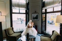 Jeune mariée avec du charme s'asseyant sur des genoux de son beau marié dans un intérieur luxueux avec les fenêtres brillantes co Photos libres de droits