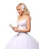 Jeune mariée avec l'argent. tenant et comptant des billets d'un dollar. belle jeune femme blonde d'isolement Images stock