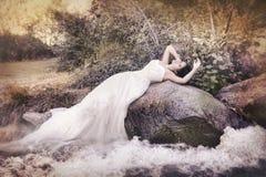 Jeune mariée avec la longue robe près des eaux Image libre de droits