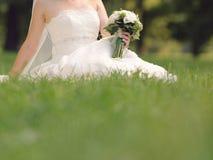 Jeune mariée avec le bouquet dans l'herbe Photographie stock libre de droits