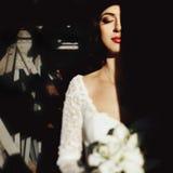 Jeune mariée avec le bouquet de lis demi dans l'ombre avec le backg industriel Photos stock