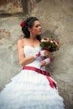 Jeune mariée avec le bouquet de mariage se penchant contre le mur Image libre de droits