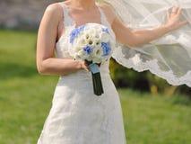 Jeune mariée avec le bouquet et le voile de vol Image libre de droits