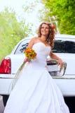 Jeune mariée avec le bouquet initial près du véhicule blanc Photographie stock