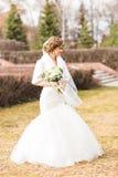 Jeune mariée avec le bouquet posant en parc ensoleillé d'automne photo libre de droits