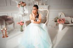 Jeune mariée avec le maquillage et fleur dans ses cheveux se reposant sur une chaise Le corps du ` s de fille peint avec le mehen photos stock