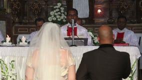 Jeune mariée avec le marié se tenant à l'autel avant le prêtre banque de vidéos