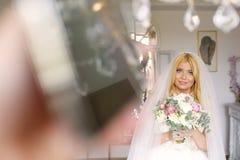 Jeune mariée avec le voile et bouquet nuptiale le jour du mariage Photo stock
