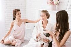 Jeune mariée avec plaisir et demoiselles d'honneur ayant la partie de poule à la maison Photos libres de droits