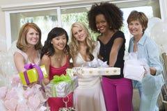 Jeune mariée avec ses amis et mère tenant des cadeaux Image libre de droits