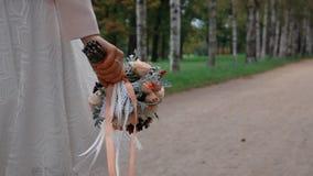 Jeune mariée avec un beau bouquet des fleurs marchant en parc banque de vidéos