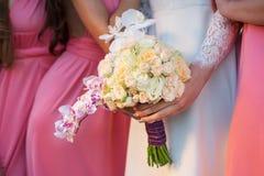 Jeune mariée avec un bouquet à disposition et amies Images stock