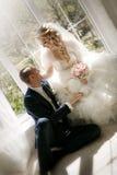 Jeune mariée avec un bouquet de mariage des roses et le marié s'asseyant à une fenêtre image stock