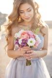 Jeune mariée avec un bouquet des fleurs dans une robe de mariage près de la mer Images libres de droits