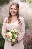 Jeune mariée avec un bouquet des plans rapprochés Photographie stock libre de droits