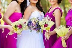 Jeune mariée avec un bouquet et les demoiselles d'honneur Photos stock