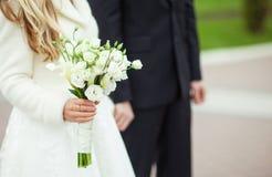 Jeune mariée avec un petit bouquet et un marié Image libre de droits